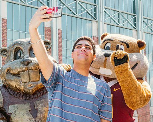 Student taking a selfie with Goldy