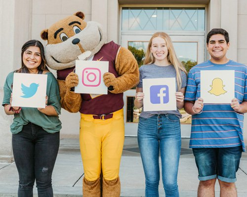 Students with Goldy holding up signs with social media logos